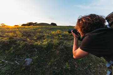 Young photographer with long brown curly hair, tattoo on his wrist and camera backpack on his back is taking picture of a sunset during golden hour in the mountains of Madeira with grove in background