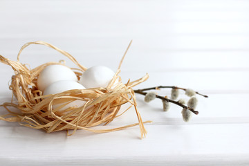 meeting Easter holiday/ three chicken eggs in a nest with willow branches, front view