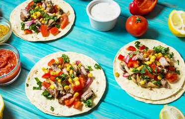 Mexican pork tacos with vegetables. Tacos al pastor on wooden blue rustic background
