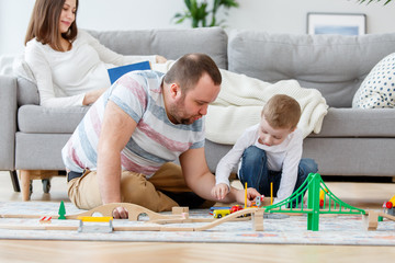 Image of father playing with son in toys sitting on floor