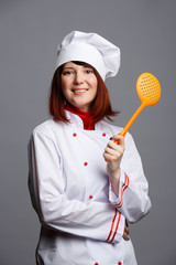Photo brunette cook in white dressing gown and cap with slotted spoon
