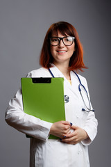 Photo of doctor girl in glasses and white coat with green folder in hands