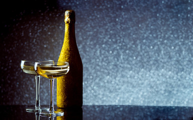 Picture of bottle of wine in gold wrapper with two wine glasses on gray background.