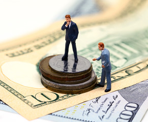 Businessman leader and finance adviser figurines. USA banknote and coin.