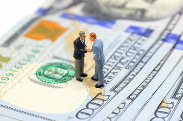 Businessmen shaking hands on american dollar. Businessmen figurines on money background.