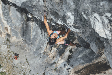 Mature strong woman climbing overhanging grey limestone roof