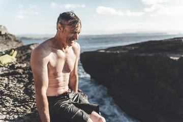 Portrait of man resting on rock