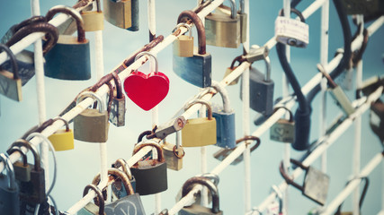Many locks of love hanging on the railing of the bridge.