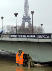 """A banner hangs from the Pont d'Alma bridge with the message, """"Get Ready for Global Warming"""", above the Zouave soldier statue that wears a life vest as high waters from rain continue to cause the Seine River to overflow its banks, in Paris"""