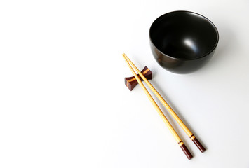 Top view of chopsticks black bowl on white table background.Flat lay