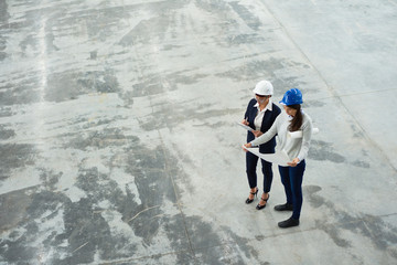 High angle view of two female engineers wearing hardhats examining floor plans in workshop of modern factory, copy space