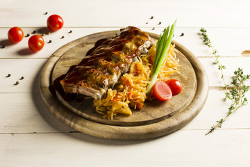 Roast ribs drizzled with sauce with stewed cabbage on a round wooden Board