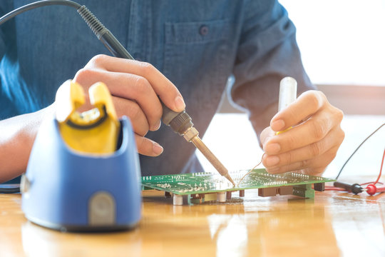 Technician repair circuit board,Use soldering equipment on circuit boards.
