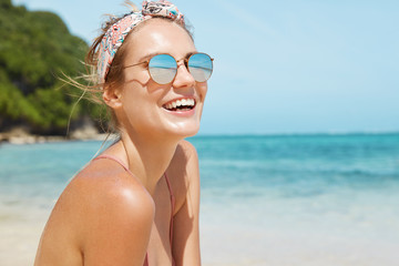 Close up shot of pleasant looking female wears headband and sunglasses, travels in tropical country, poses against warm peaceful ocean, blue sky and rocky cliff in background. Good relaxation Wall mural
