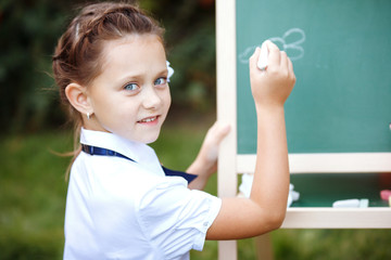 Schoolgirl with a chalkboard in the park.