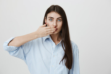 Indoor shot of young stylish woman covering her mouth with hand, looking anxious with lifted eyebrows, standing over gray background. Trendy woman with stylish manicure promises to keep mouth shut