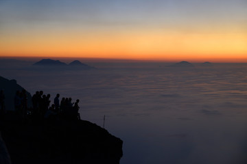 Pleople on the summit of Volcano Stromboli enjoying the sunset and view of the Aeolian Islands, Sicily, Italy