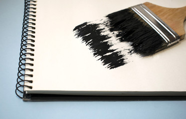 Open notebook with brush on a blue background. Black paint