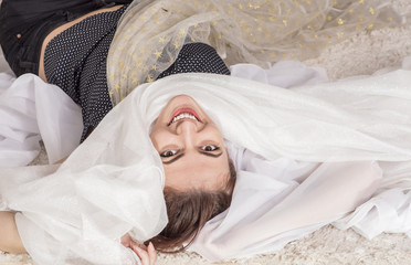 Portrait of a young woman lying on floor daydreaming about wedding dress with white fabric