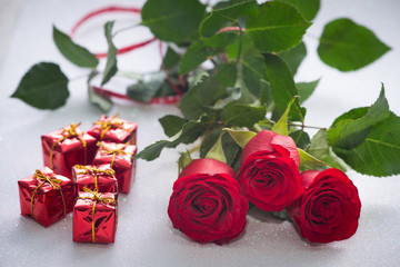 occasional beautiful red roses with tiny boxes of gifts on the shiny background