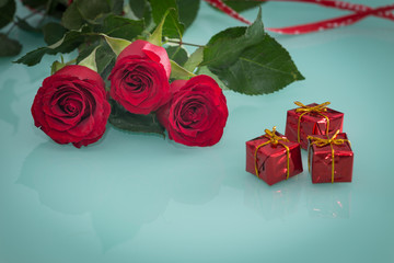 occasional beautiful red roses with tiny boxes of gifts on the background