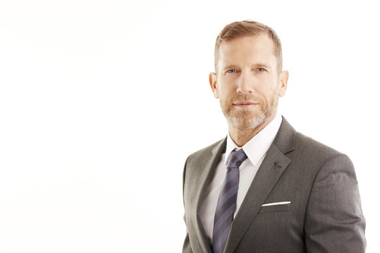 Executive businessman portrait. Successful smiling lawyer wearing suit and looking at camera while standing at isolated white background with copy space.