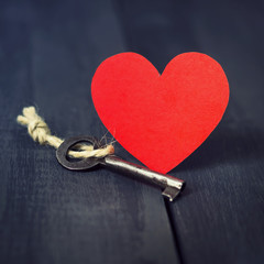 Red paper heart old key and presents on a dark wooden background. St. Valentine's Day. Copy space.