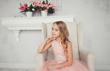 Beautiful little girl in charming dress sitting on the armchair