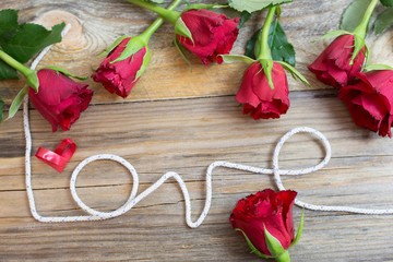 Beautiful red roses with love and red ribbon heart shape on wooden background.
