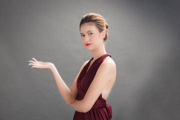 Beautiful woman wearing red dress and showing product on hand in studio gray background. Action for presenting your product