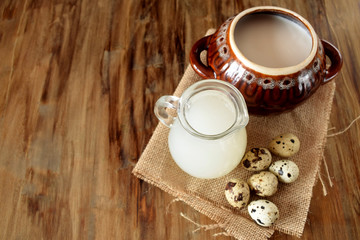 Milk whey, quail eggs and a clay pot on a wooden background. Farm products
