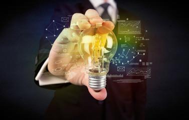 businessman holding glowing glass light bulb