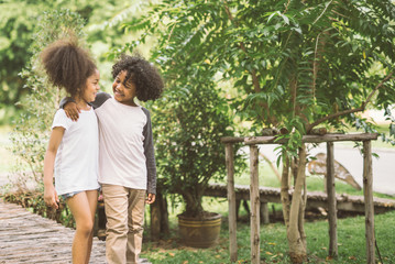 Children Friendship Togetherness Smiling Happiness Concept.Cute african american little boy and girl hug each other in summer sunny day