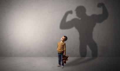 Muscleman shadow behind waggish little boy