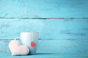 Cup of tea with fabric heart on wooden table