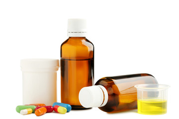 Bottles, measuring plastic cup with medical syrup and capsules on white background