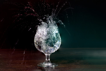 Ice fall to Soda water in glass cup splash and splatter on dark background