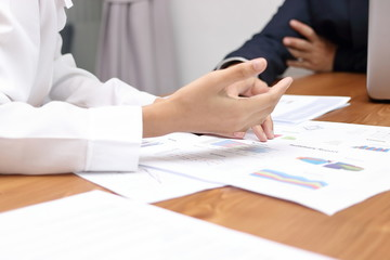 Selective focus on hands of business people discussing charts between meeting in conference room