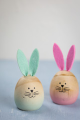 Cute little wooden Easter bunny amongst dyed eggs