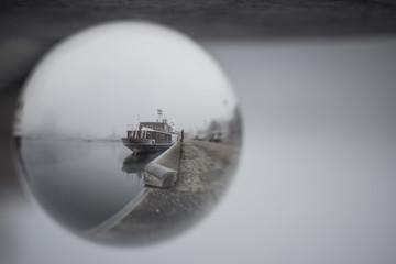 Schiff im Hafen von Kiel durch eine Glaskugel betrachtet