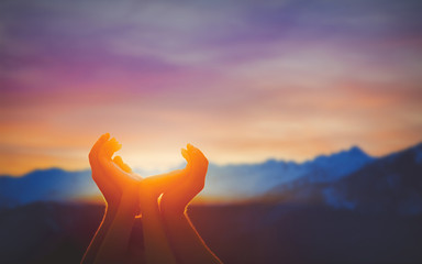 Human hands praying together at dawn