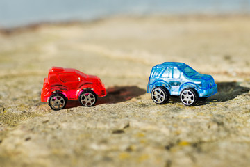 blue and red toy cars with stone background