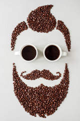 Bearded hipster man made of coffee beans with glasses made of cups of coffee