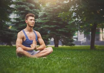 Young man practicing yoga sitting in padmasana