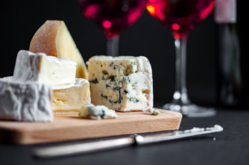 Assortment of cheeses  on a wooden plate and two wine glasses.