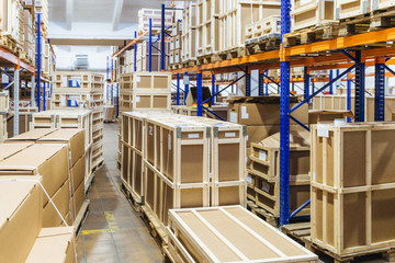 Rows of shelves filled with cardboard boxes. Warehouse transport and logistics company. Storage of retail. Large hangar. Big containers. Goods inside.