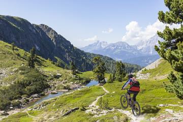 Mountainbiker downhill on Reiteralm with mountain Dachstein in Styria Austria