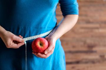 femme en robe bleu et pomme rouge