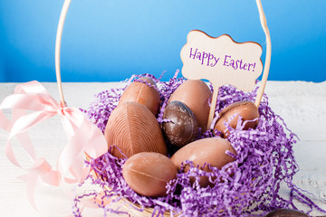 Image of chicken, chocolate eggs, purple decorative paper in basket ,wish for happy Easter