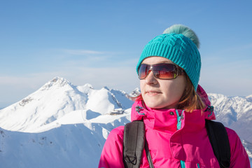 portrait of   young woman in sunglasses on background snowy mountain